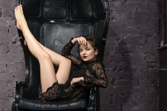 Girl posing in a big black leather chair. Stock Image
