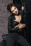 Girl posing in a big black leather chair. Royalty Free Stock Image