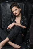 Girl posing in a big black leather chair. Stock Photography