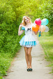 Girl posing with a big bunch of colorful balloons Stock Photography