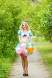 Girl posing with a big bunch of colorful balloons Stock Photos