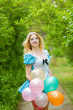 Girl posing with a big bunch of colorful balloons Royalty Free Stock Photos