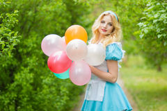 Girl posing with a big bunch of colorful balloons Stock Images