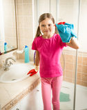 Girl posing with blue cloth while cleaning sink at bathroom Royalty Free Stock Image