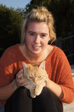 Girl Posing with Cat. Pretty girlposing  with her pet ginger cat outside on a sunny day Royalty Free Stock Image