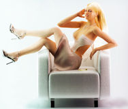 Girl posing on chair. Pretty blonde on silver chair posing, cocktail spill Royalty Free Stock Images