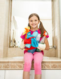 Girl posing with cleanser bottles and rags posing at bathroom. Portrait of smiling girl posing with cleanser bottles and rags posing at bathroom Royalty Free Stock Image