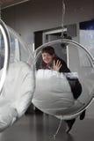 Girl posing in glass chair Stock Photos