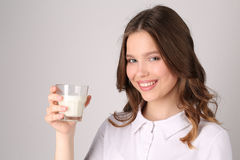 Girl posing with glass of milk. Close up. White background Royalty Free Stock Image