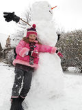 Girl posing with her big snowman. Royalty Free Stock Photo