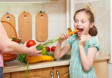 Girl posing in home kitchen with fresh fruits and vegetables, eating a carrot - healthy eating concept royalty free stock image