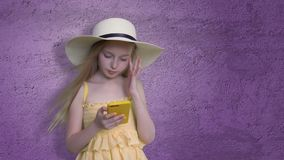 Girl Posing with Mobile Phone on Violet Background. Girl Posing with Mobile Phone on Violet Lilac Background. Child in Hat and Yellow Dress Hold Telephone in stock video