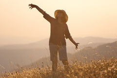 Girl posing on mountain and having fun on idyllic field at sunse Royalty Free Stock Photos
