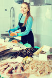 Girl posing near display with fish Royalty Free Stock Photos