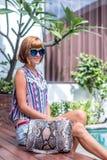Girl posing near the swimming pool with a big super fashionable snakeskin python handbag. Tropical island Bali.  royalty free stock photo