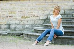 Girl posing near wall. Young beautifull girl sitting on vintage footsteps with closed eyes near old grungy wall stock photos