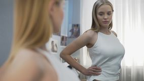 Girl posing in new white shirt near mirror, adolescent development, future model. Stock footage stock video footage