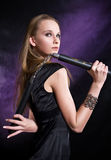 Girl posing with nunchaku. Beautiful young girl posing with nunchaku royalty free stock photography