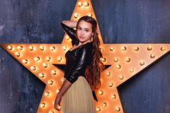 Girl Posing On A Background Of Gold Star Royalty Free Stock Photography
