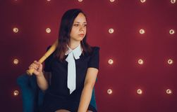 Girl posing on a red background with a baseball bat in his hands, the concept of a bully or athletes royalty free stock images