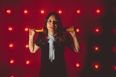 Girl posing on a red background with a baseball bat in his hands, the concept of a bully or athletes royalty free stock photography