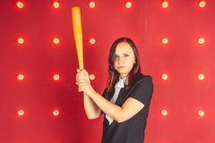 Girl posing on a red background with a baseball bat in his hands, the concept of a bully or athletes stock photos