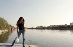Girl posing on the river. Girl on the river by the city Royalty Free Stock Image