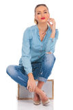Girl posing seated in studio on a box with legs crossed Stock Photo