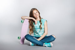 Girl posing with skateboard sitting in the studio. Joy, smile, positive emotions Stock Images