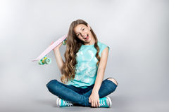 Girl posing with skateboard sitting in the studio. Joy, smile, positive emotions Royalty Free Stock Photos