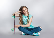 Girl posing with skateboard sitting in the studio. Joy, smile, positive emotions Stock Photo