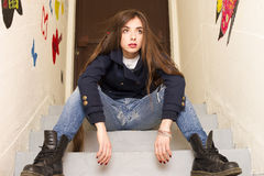 Girl posing on the staircase. Relaxed and annoyed against big door and graffiti wall Royalty Free Stock Image