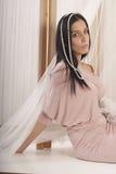 Girl posing in the studio like princess. Girl posing in the studio sitting on white board royalty free stock photo
