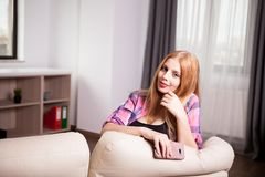 Girl posing to the camera with a phone in hands. In the living room Stock Images