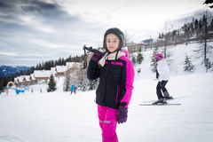 Girl posing on top of ski slope with ski equipment Stock Images