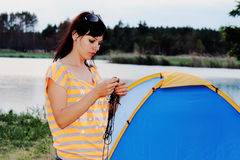 Girl posing tourist tent. Camp in the tent - family setting a tent on the camping royalty free stock photo