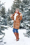 Girl posing in winter park at day. Fir trees with snow. Redhead woman full length. Stock Photo