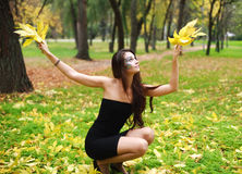 Girl posing with yellow leaves Stock Photography