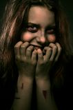 Girl possessed by a demon with a sinister smile Royalty Free Stock Photos