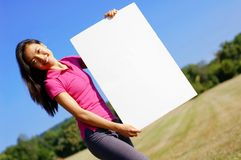 Girl With Poster. Happy asian girl holding a blank poster royalty free stock photography