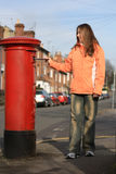 Girl posting letter to red british postbox. On street Royalty Free Stock Image