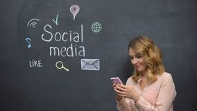 Girl posting message in social media using cell phone, global connection in net stock footage