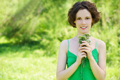 Girl with posy outdoors. Outside portrait of beautiful young curly woman with bunch of flowers in her hands stock photos