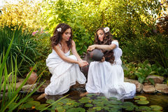 Girl pour water from a jug. Two sisters in white dresses at the pond with water lilies. Girl pours water from small clay jars in the hands of her sister Stock Images