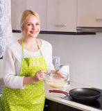 Girl pouring dough in pan Stock Images