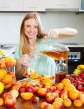 Girl pouring fresh beverages with fruits Stock Photography