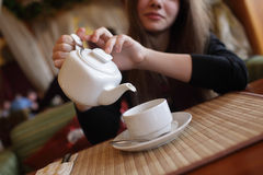 Girl pouring green tea Stock Images