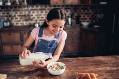Girl pouring milk into the bowl of corn flakes royalty free stock image