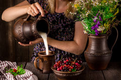 The girl pouring milk from a jug into a cup and a bowl with berries on a wooden table. Jug with flowers. Royalty Free Stock Photo