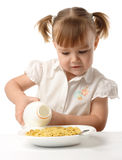 Girl pouring milk in a plate with corn flakes Stock Photos